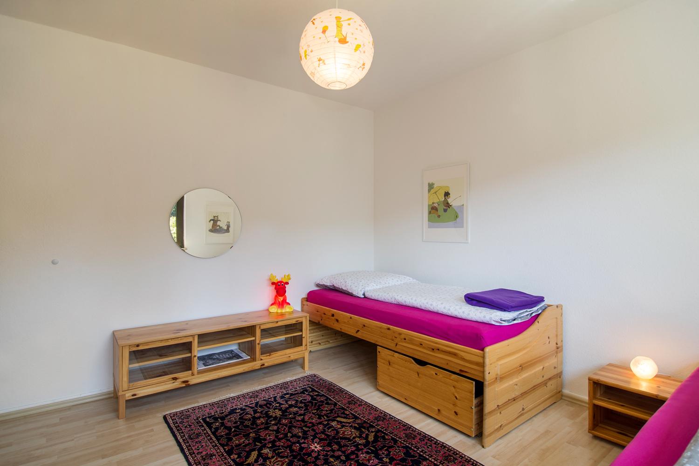 Bett, Sideboard und Spiegel im Kinderzimmer