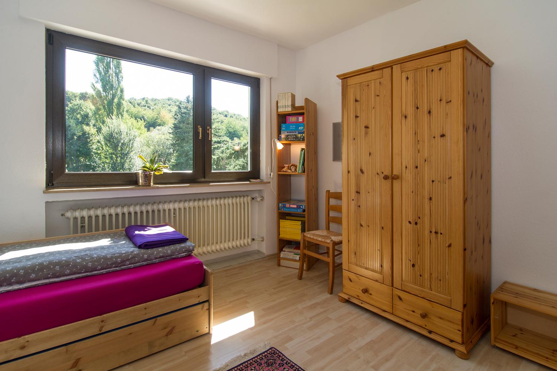 Bett, Schrank und großes Fenster zum Garten