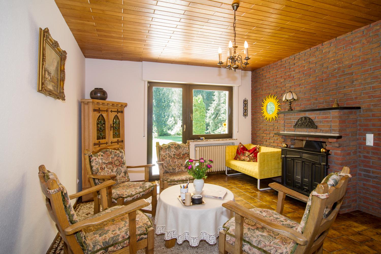Kaminzimmer mit Stühlen und gelbem Sofa