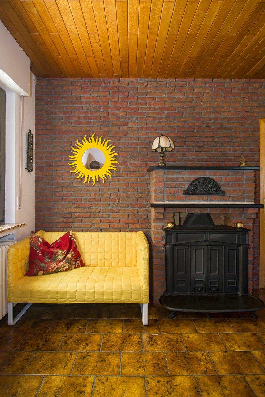 Gelber Sonnenspiegel im Kaminzimmer über dem gelben Sofa