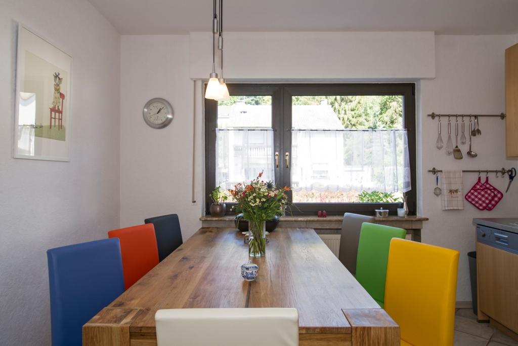 Küche: großer Esstisch mit bunten Stühlen