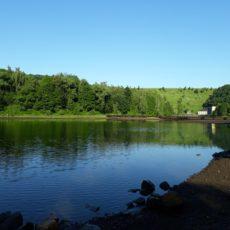 Blick über den See zum Staudamm und gelben Kraftwerk